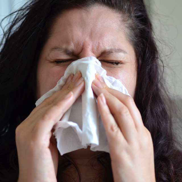 """Woman blowing her nose hard into a tissue at home"" stock image"