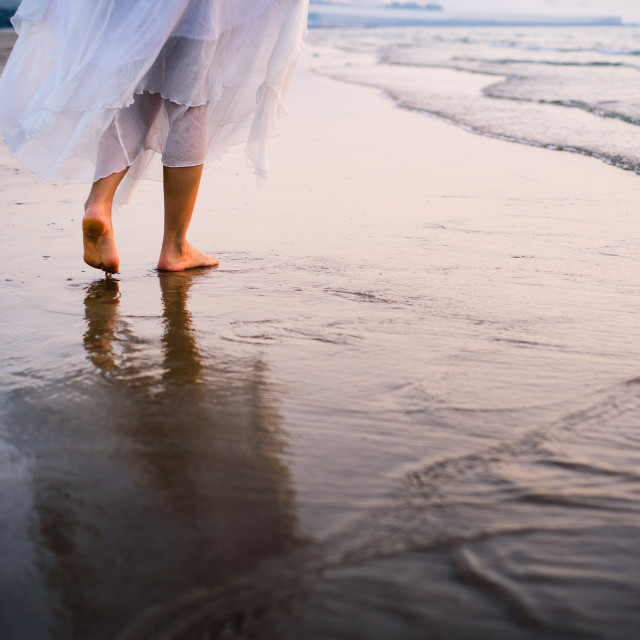 """Girl walking on the beach wearing white dress"" stock image"