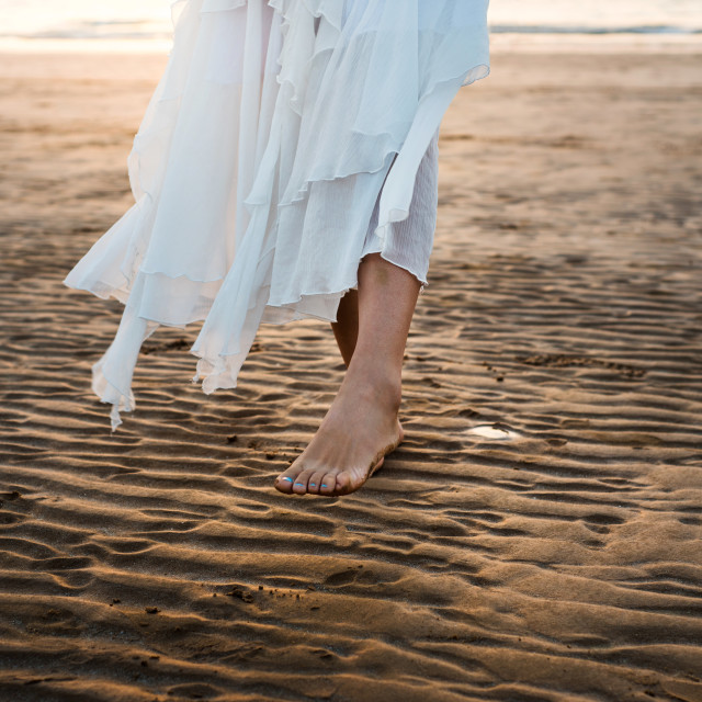 """Girl in white dress walking on the beach"" stock image"