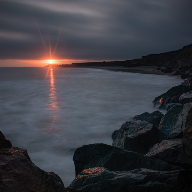 """Slice. Dawn over rocks at Happisbugh beach"" stock image"