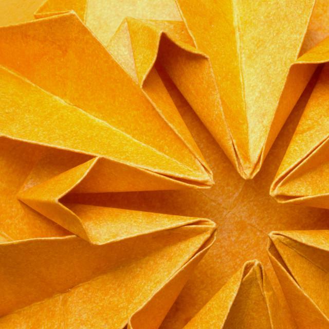 """Textured orange paper origami flower"" stock image"