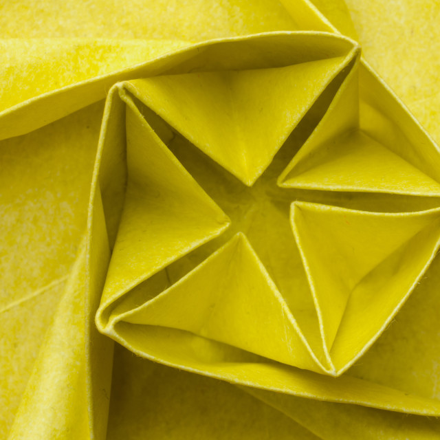 """Spiral shaped yellow paper origami flower"" stock image"