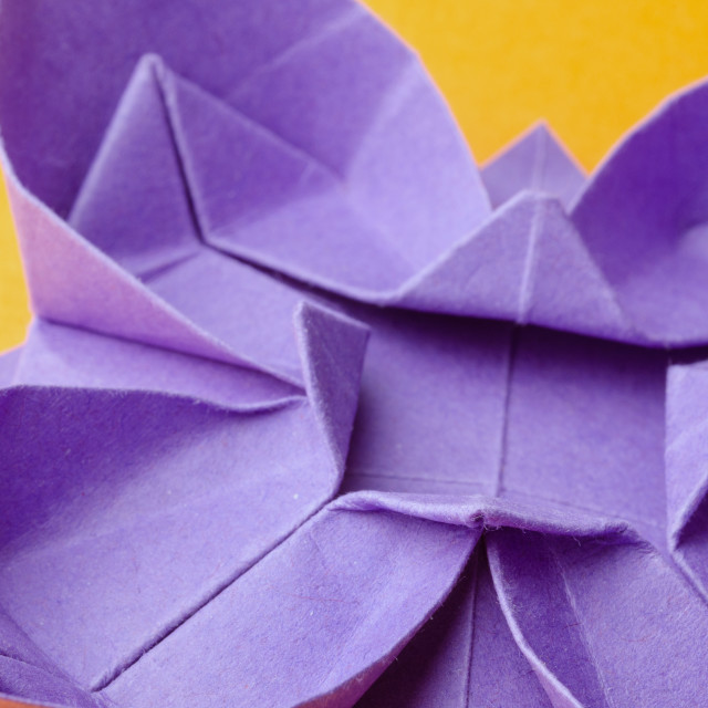 """Purple paper origami flower on orange background"" stock image"
