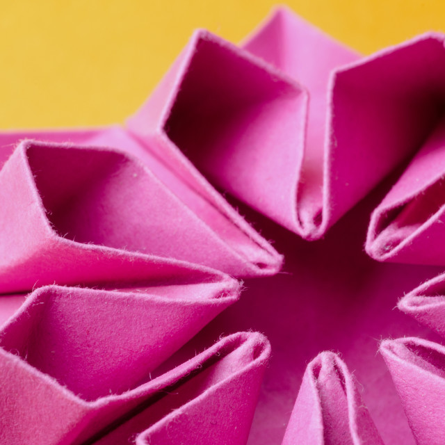 """Pink paper origami flower on orange background"" stock image"
