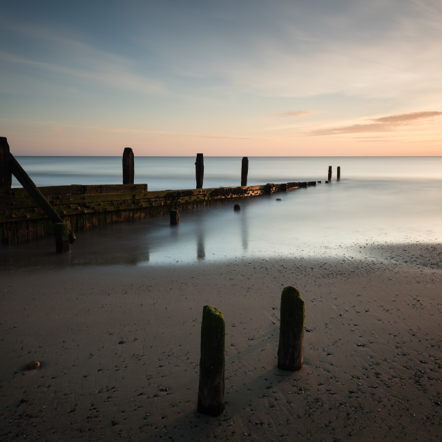 """Mundesley morning I Pastel sunrise over old groyne i"" stock image"