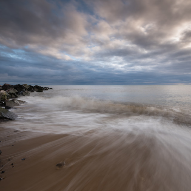 """Happisburgh beach morning IV Swirling waves around coastal rocks, cloudy..."" stock image"