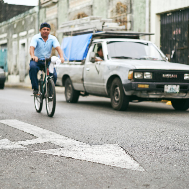 """Merida / Yucatan, Mexico - June 1, 2015: The focus of arrow sign on the street with the man riding the bicycle and car blurry in background in the city of Merdia, Yucatan, Mexico"" stock image"