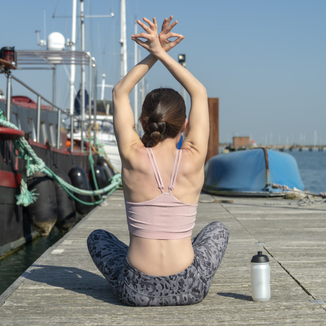 """woman practicing yoga on a wooden pontoon by the water with yachts and boats."" stock image"
