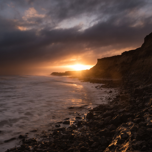 """Breaking. Dawn at Happisburgh beach I Sun breaking through dramatic clouds"" stock image"