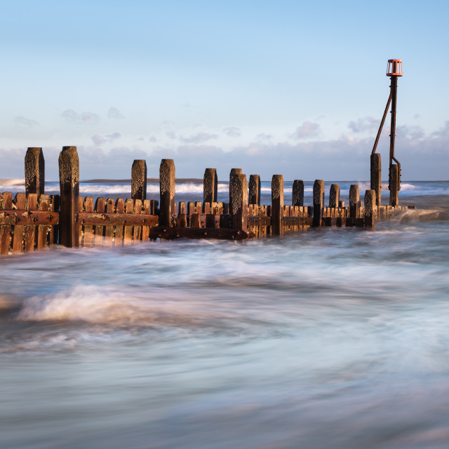 """Morning at Mundesley beach XII. Groyne and swirling sea iii"" stock image"