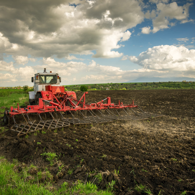 """""""Tractor plowing fields. Preparing land for sowing."""" stock image"""