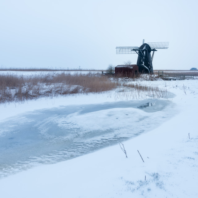 """Snowy morning at Herringfleet Mill IV. Frozen pool and snow in front of windmill"" stock image"