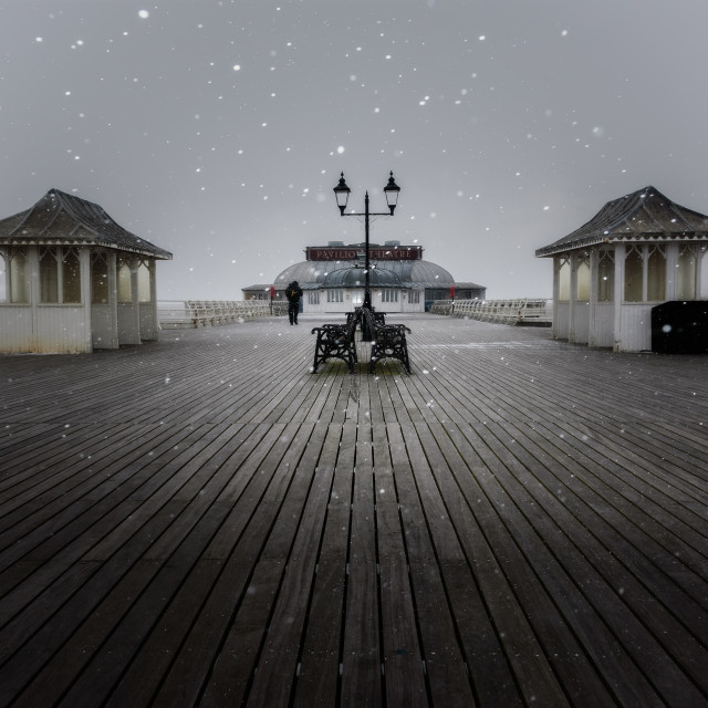 """Flurry. Snow flurry on Cromer pier, with figure"" stock image"
