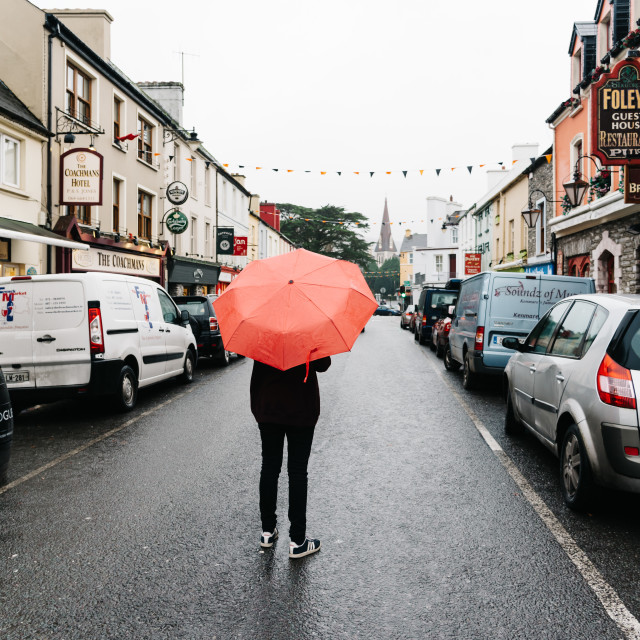 """""""Woman with red umbrella in the middle of street in small Irish"""" stock image"""