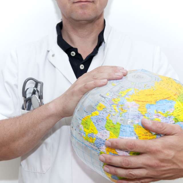 """Doctor with a beach ball globe, concept global health care."" stock image"