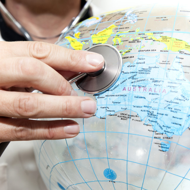 """Doctor with a beach ball globe with Australia facing concept global health..."" stock image"