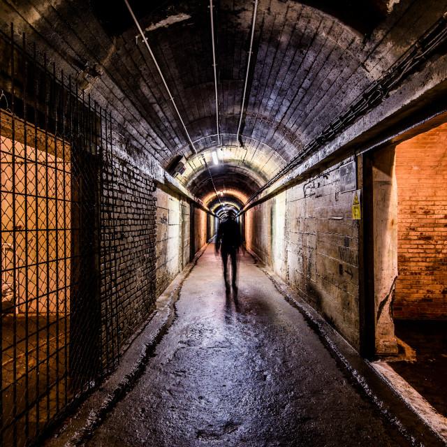 """A tourist walking through The Underground German Hospital in Guernsey"" stock image"