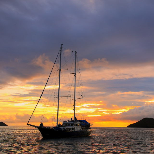 """""""Silhouetted tourist sailboat at sunrise anchored near Chinese Hat island in..."""" stock image"""