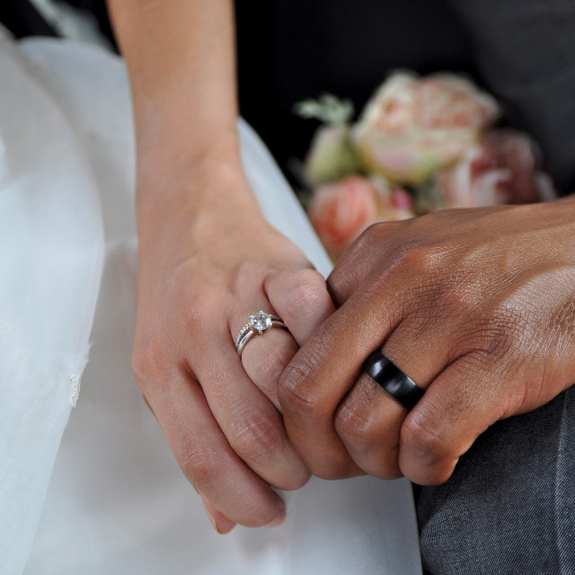 """Just Married Interracial Couple Holding Hands Wearing Wedding Rings"" stock image"