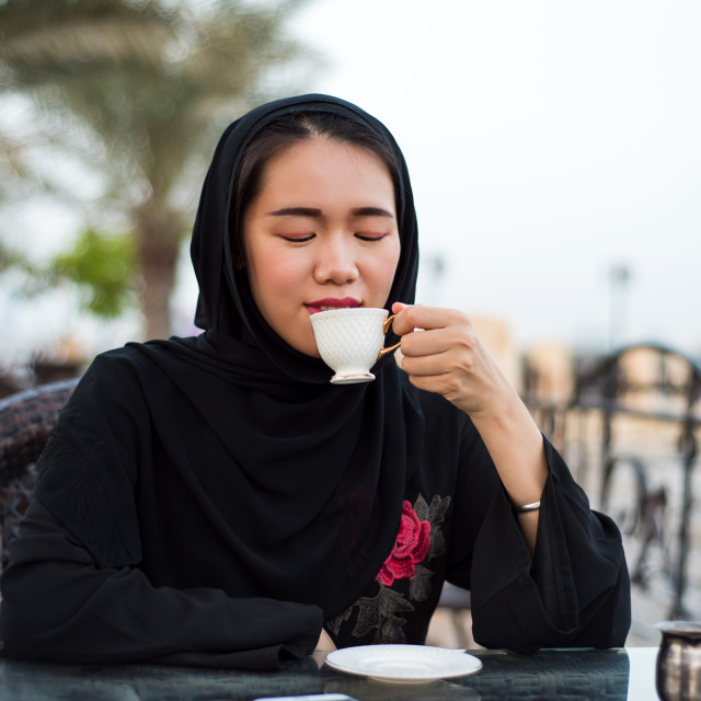 """Muslim woman having a cup of coffee outdoors"" stock image"