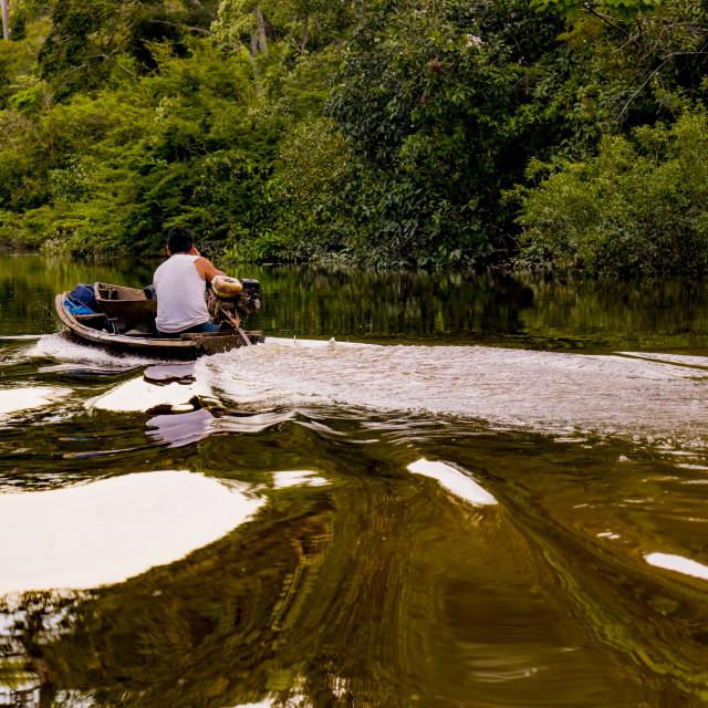 """Boat cruising through amazonian river with indigenous captain, waves reflect"" stock image"