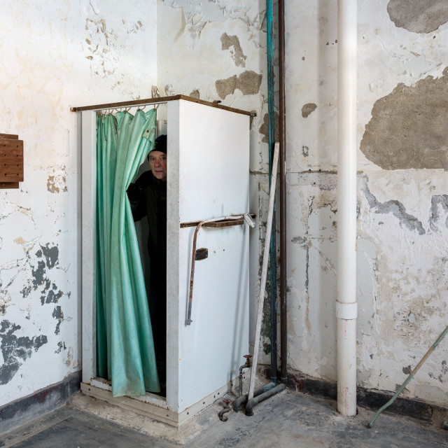 """Abandoned shower and man inside Trans-Allegheny Lunatic Asylum"" stock image"