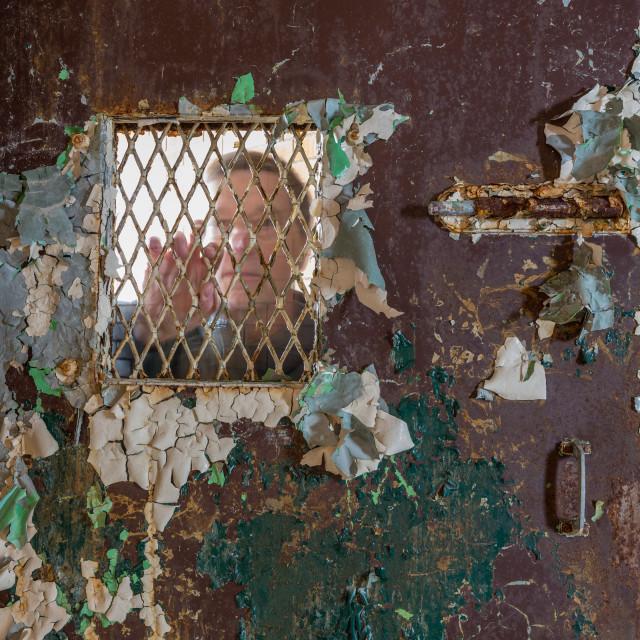"""Senior man behind locked barred door in cell"" stock image"