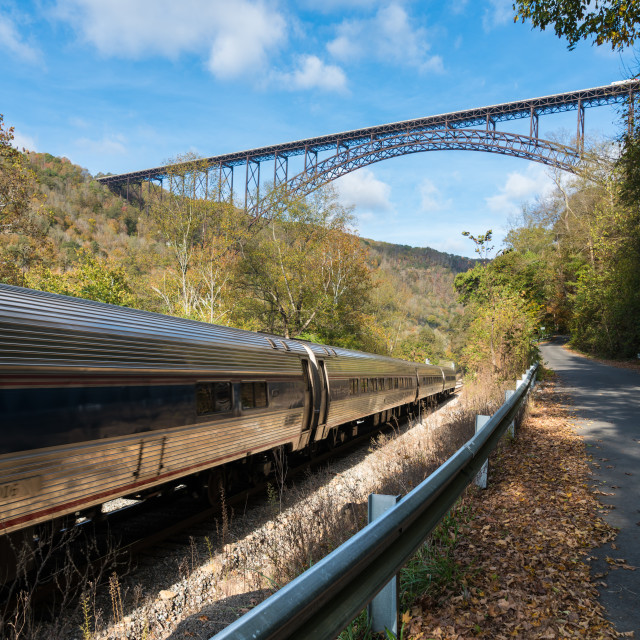 """Train runs under the New River Gorge Bridge in West Virginia"" stock image"