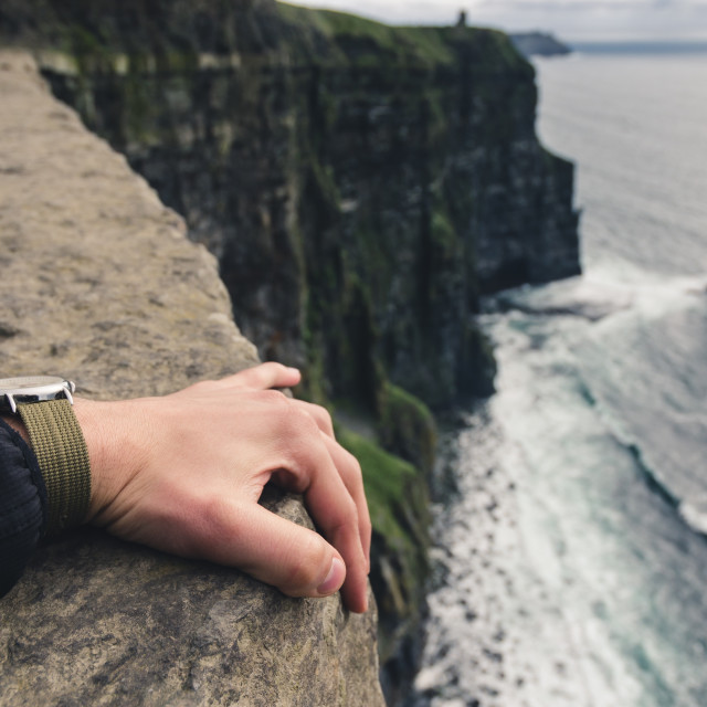 """holding tight at the edge of a cliff"" stock image"