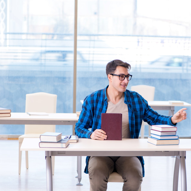 """""""Student studying in the empty library with book preparing for ex"""" stock image"""