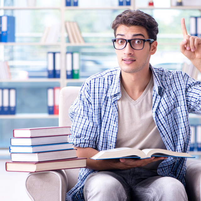 """""""Student reading books and preparing for exams in library"""" stock image"""