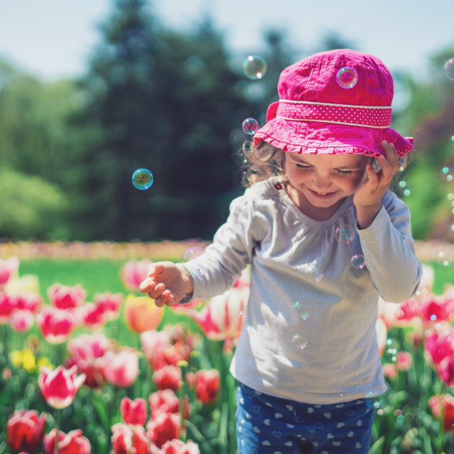 """A little girl blowing soap bubbles in summer park"" stock image"