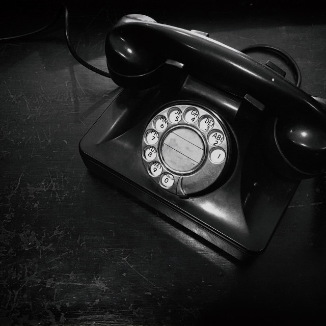 """""""Black and white antique dial telephone on table"""" stock image"""