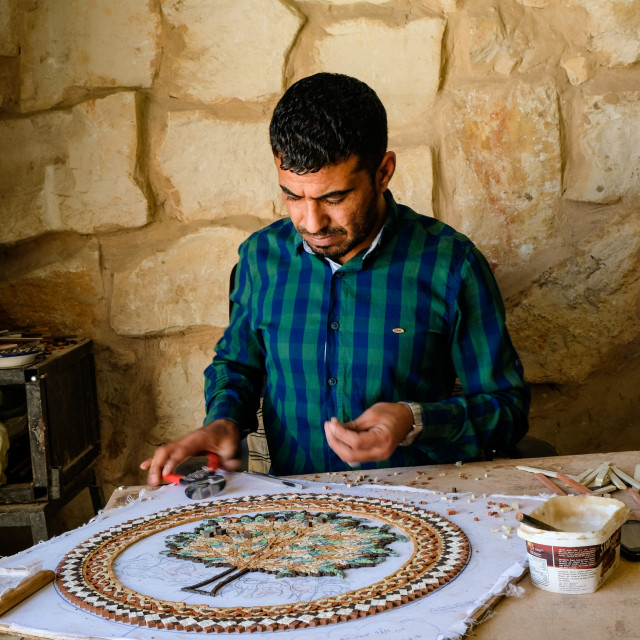 """Craftsman working on a mosaic representing a colorful tree in Madaba"" stock image"