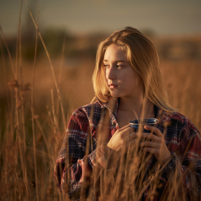 """Young Woman With a Coffee Cup Standing Alne iin a Field"" stock image"