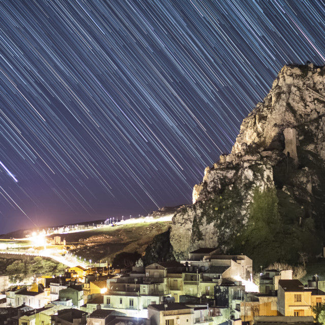 """Sicilian mountain peak and village in star trails."" stock image"