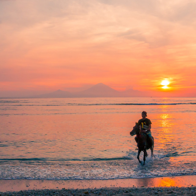 """""""An indonesian man riding in the water at sunset"""" stock image"""