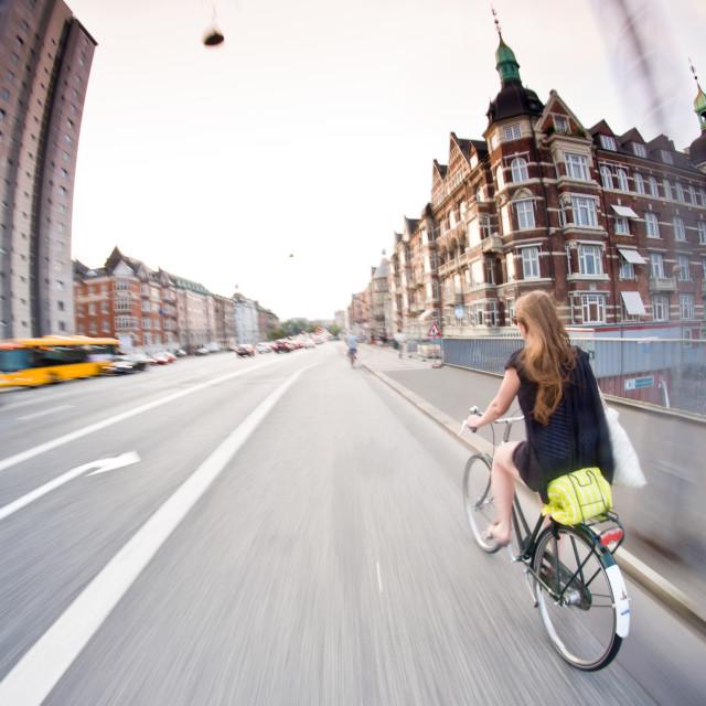 """typical Copenhagen: pretty girl riding bike, old buildings around. Denmark"" stock image"