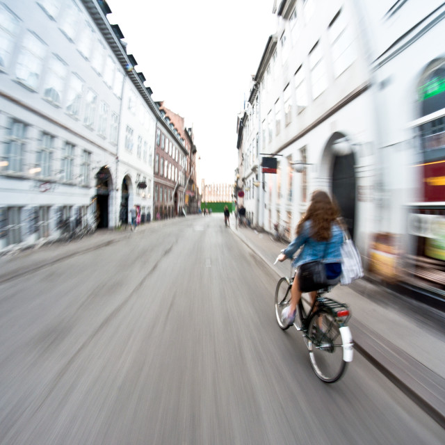"""Girl on bike riding fast - motion blur"" stock image"