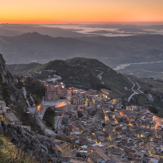 """Mountain top village in Sicily illuminated by early sun."" stock image"
