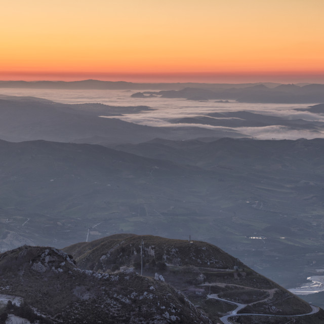 """Sicilian valleys covered in fog illuminated by sunrise."" stock image"
