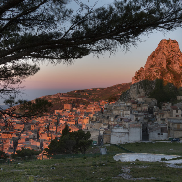 """Mountain top Sicilian village framed by a tree at sunrise."" stock image"