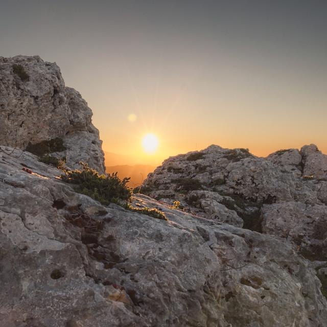 """Sun peaking through the rocks at sunrise."" stock image"