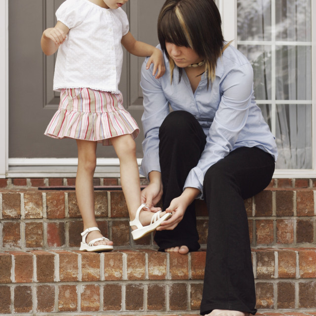 """""""Helping Young Girl With Shoes"""" stock image"""