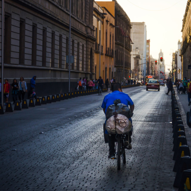 """Man riding a bicycle on the streets of Mexico city at golden hour"" stock image"