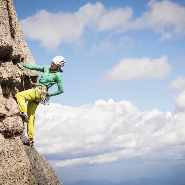 """Woman rock climbing a trad route at Corbet's Couloir in Jackson Hole, Wyoming"" stock image"