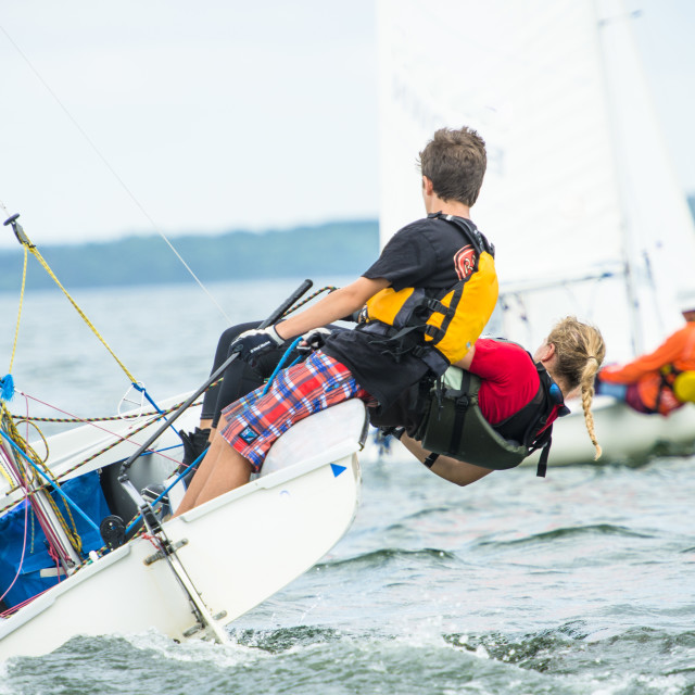 """Teenage Boy and Girl working as a team during Summer Sailing"" stock image"