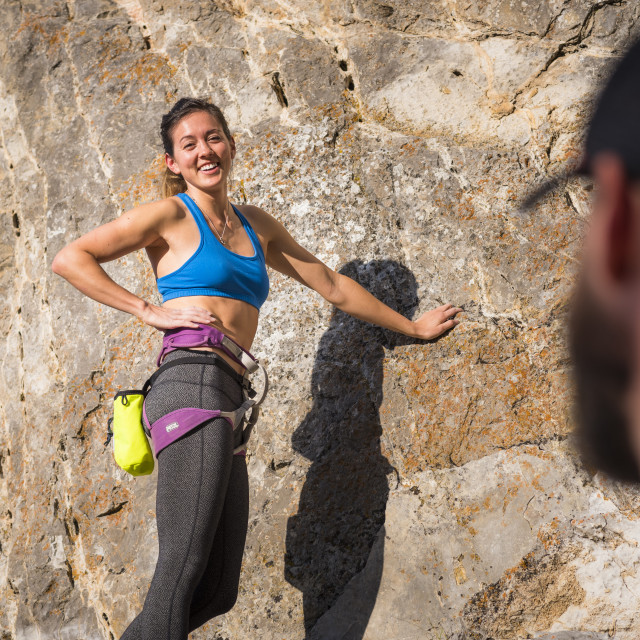 """Athletic Woman Laughing before a Rock Climb"" stock image"