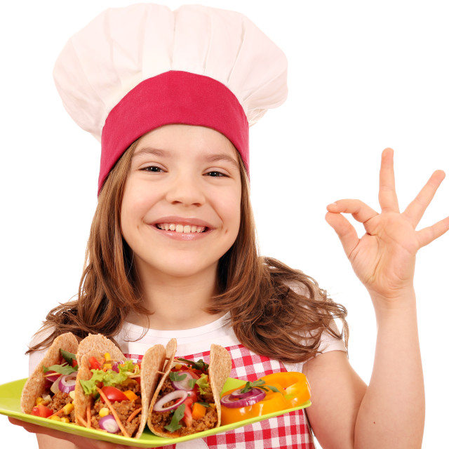 """Happy little girl cook with tacos fast food and ok hand sign"" stock image"