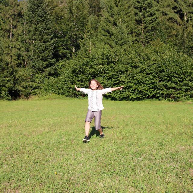 """happy little girl running on field"" stock image"